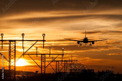 canvas print picture Avión aterrizando en un aeropuerto al atardecer