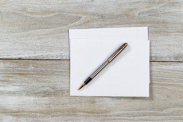 Wooden Desktop with white envelope and pen