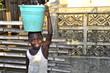 Leinwandbild Motiv Afrikanisches Mädchen trägt Eimer mit Wasser
