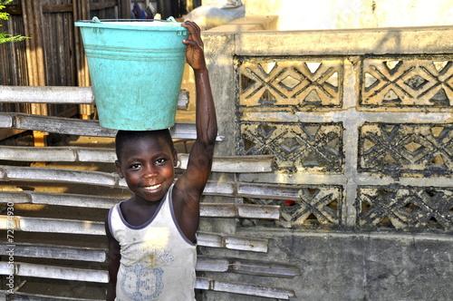 Leinwanddruck Bild Afrikanisches Mädchen trägt Eimer mit Wasser