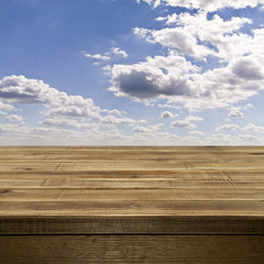 Empty wooden table top against a blue sky with fluffy white clou