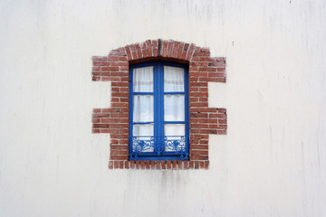 Blue Window frame edged with bricks in Brittany