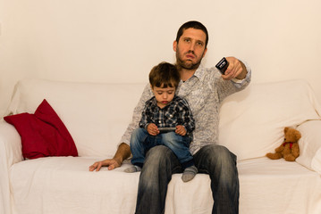 Bored father watching tv with son on a white sofa