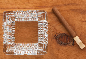 Glass ashtray with cigar  on a wooden surface