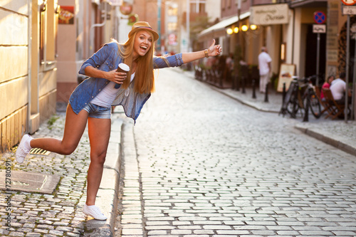 Young stylish woman drinking coffee to go in a city street - 72780591