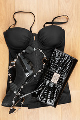 Black  lingerie, shoes and bag  lying on the laminate