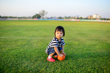 Asian girl playing ball in green field.
