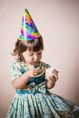 little girl eating cake in a festive cap in vintage style