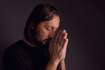 Adult bearded man praying in dark room