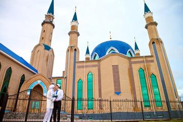 Мусульманская пара стоит возле мечети