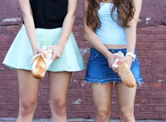 Two young women having fun with bread