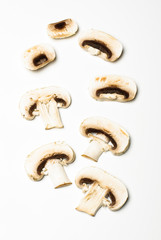 Raw champignon mushroom slices on the bright background