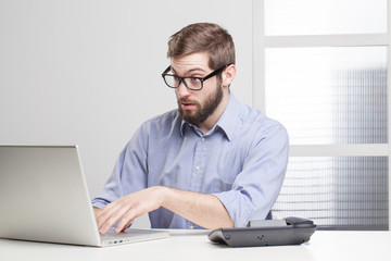 Young businessman in shock looking at his laptop
