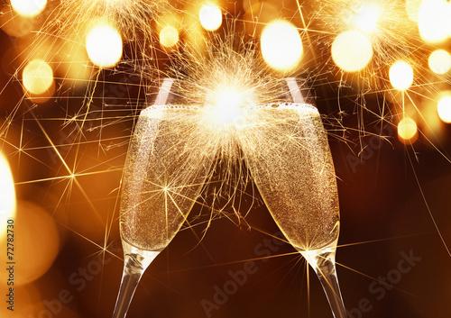 Leinwanddruck Bild Glasses of champagne with sparklers