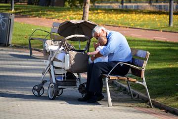 abuelo dando de comer a su nieto en un parque