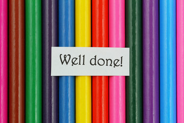 Well done card on background made of colorful pencils