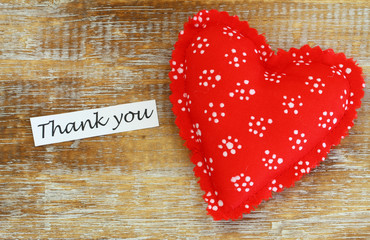 Thank you card with red heart on wooden surface