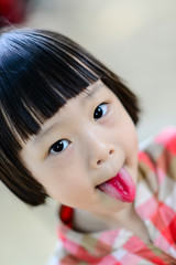 Cute Asian girl showing her red tongue.