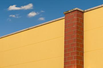 Eine gelbe Mauer unter blauem Himmel