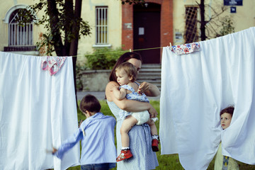 woman with children in garden hanging laundry