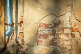 Cracked house wall with hanging metal drainpipe. poster