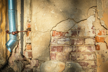 Cracked house wall with hanging metal drainpipe.