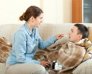 Girl giving  medicament to unwell husband
