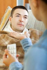 women giving pills to diseased man
