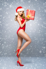 Young and sexy Santa girl in the red swimsuit with a present