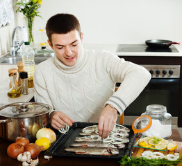 man cooking raw fish and onion