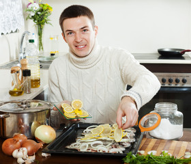 Handsome man with  fish on roasting pan