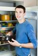 Man with pan near fridge