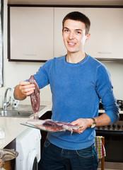 Happy guy holding raw calamari