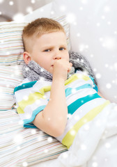 ill boy with scarf lying in bed and coughing