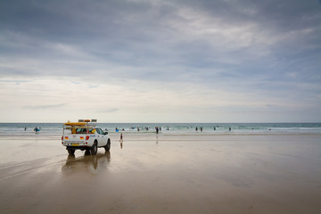 Lifeguard patrolling a beach at Porthtowan in Cornwall, UK