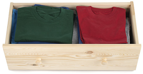 T-Shirts in wooden drawer isolated on white background.