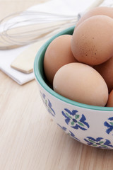 Brown Eggs in a White and Blue Bowl