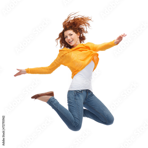 Leinwanddruck Bild smiling young woman jumping in air
