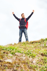 tourist with beard and backpack raising hands