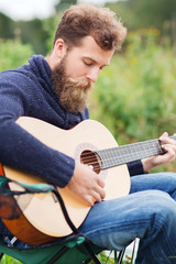 man with beard playing guitar in camping