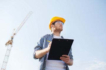 builder in hardhat with clipboard outdoors