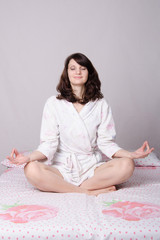 Woman meditating sitting on the bed