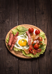 Fried egg with ham and tomatoes on old wooden table