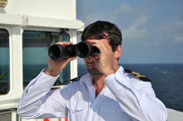 navigator on navigation bridge during his watch  with binocular