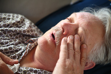 Senior man lying down with flu