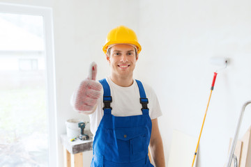 smiling young builder in hardhat showing thumbs up