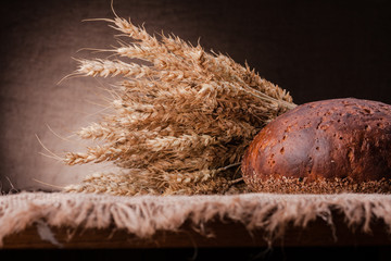 Loaf of bread and rye ears still life