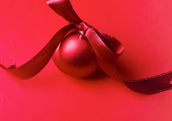 Red christmas ball, isolated on red background.