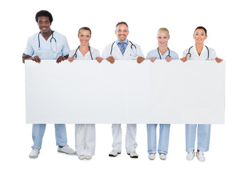 Confident Medical Team Holding Blank Billboard
