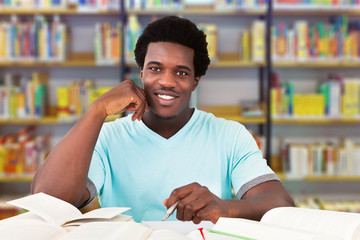 Male University Student Studying In Library